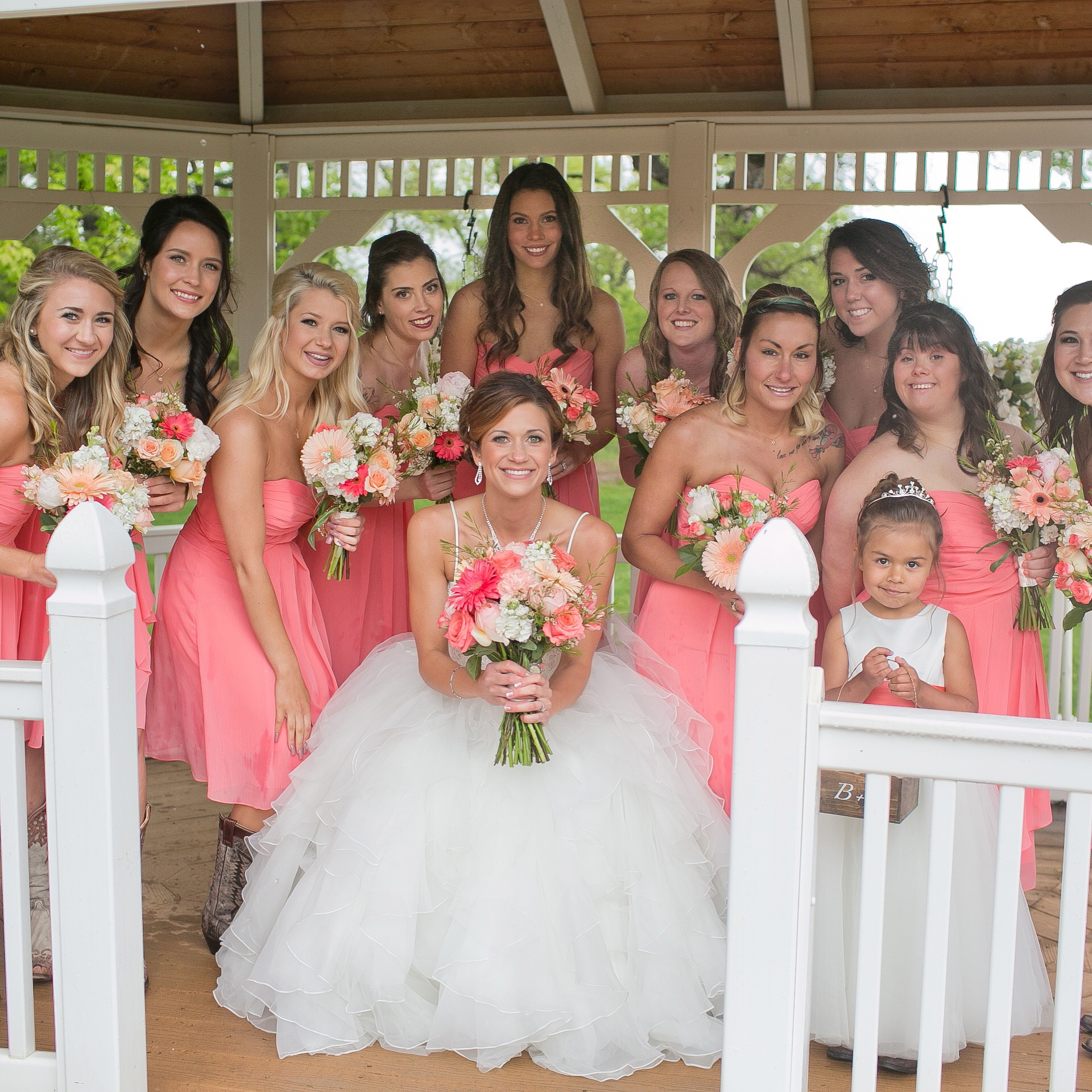 bride posing with bridesmaids in pink gowns
