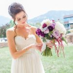 bride holding a purple bouquet of flowers